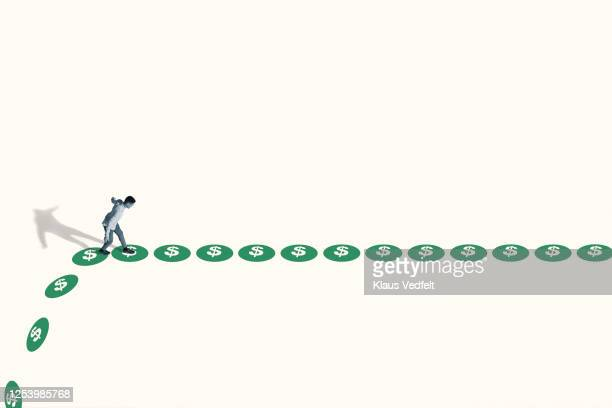 watchful young man walking on green dollar signs - oresund region stock pictures, royalty-free photos & images