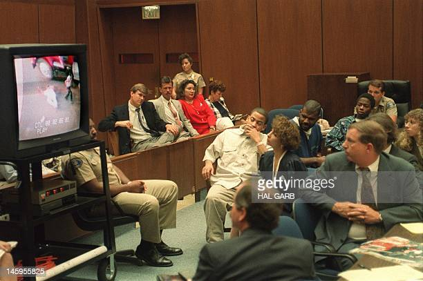 Watching a television monitor showing footage shot by amateur photographer Timothy Allen Goldman at their pre-trial hearing 31 July 1992 are Damian...