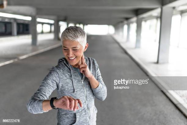 watching her heart rate - checking sports stock pictures, royalty-free photos & images