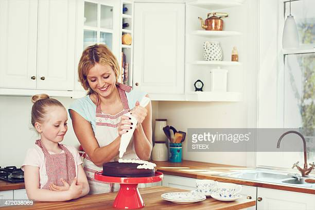 watching mom ice the cake - decorating a cake stock pictures, royalty-free photos & images