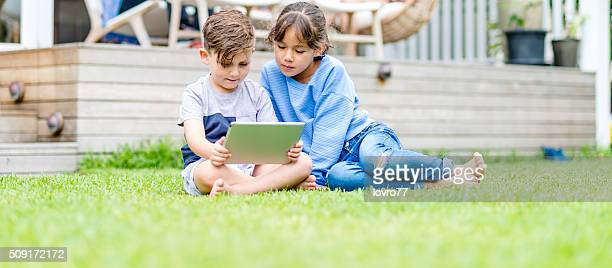 Watching something on a digital tablet on grass