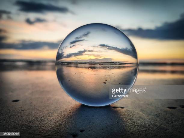 watching sunrise throught a lens ball - riviera romagnola - sports ball stock pictures, royalty-free photos & images