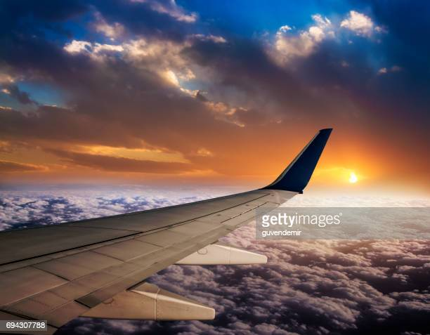 watching sunset on flight - aircraft wing stock pictures, royalty-free photos & images
