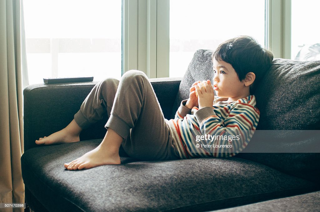 Watching television, eating fruit : Stock Photo