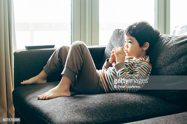 watching television, eating fruit - peter lourenco stock pictures, royalty-free photos & images