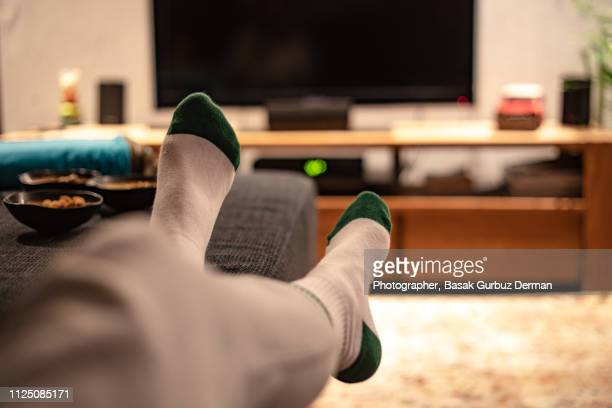 watching television relaxed at home - feet up stock pictures, royalty-free photos & images