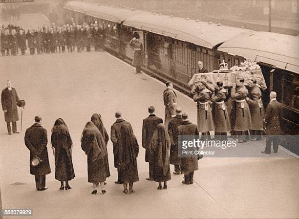 Watching the coffin covered by the Royal Standard and surmounted with the Imperial Crown lifted from the train royal mourners among whom Queen Mary...