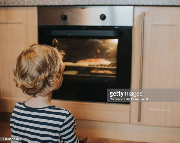 watching the oven - looking stock pictures, royalty-free photos & images