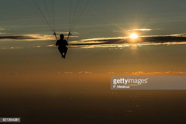 Watching the rising sun from a paraglider