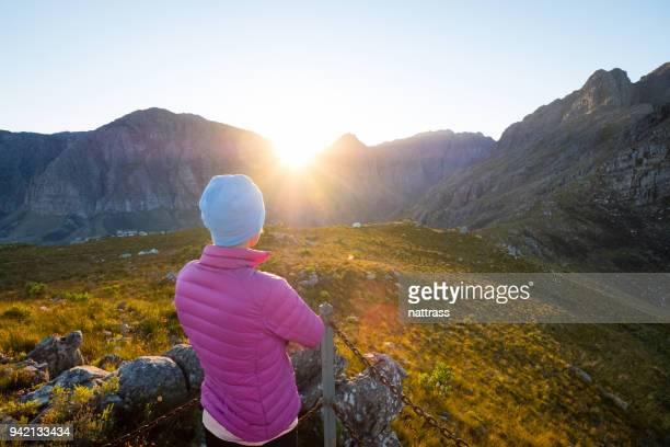 Beobachten den Sonnenaufgang über den Bergen