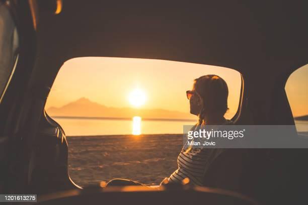 observando o pôr do sol na praia - reflexo de luz efeito fotográfico - fotografias e filmes do acervo