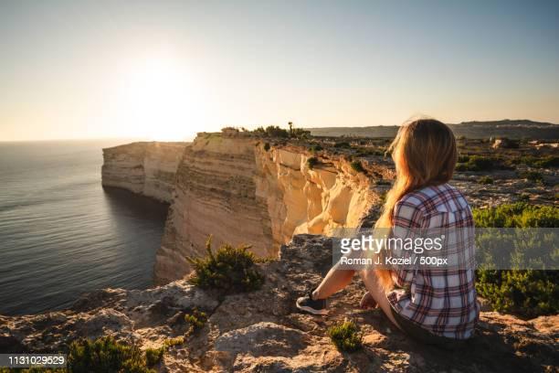 watching the sunset over cliffs of gozo - insel gozo malta stock-fotos und bilder