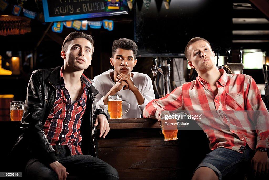 Watching TV in bar. men drinking beer sitting  bar : Stock Photo