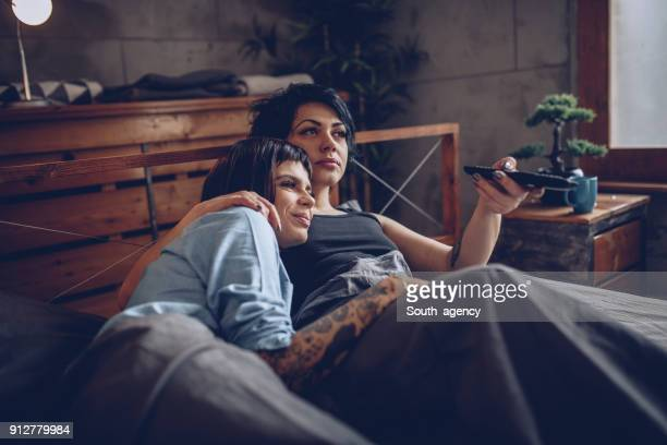 watching tv in bed - lgbtq  and female domestic life stock pictures, royalty-free photos & images
