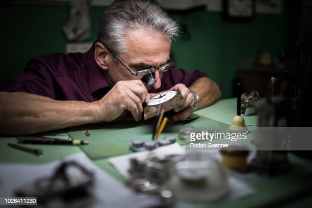 A watchmaker examines a watch with a magnifying glass on August 16 2018 in Weisswasser Germany