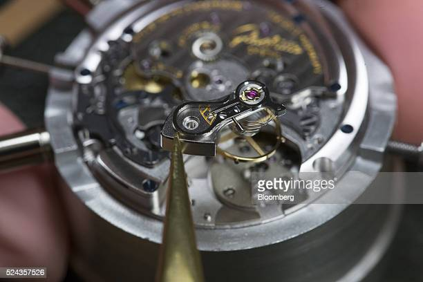 A watchmaker prepares to position an escapement wheel during the assembly of a Senator Chronograph Panorama Date luxury wristwatch at the Glashuette...