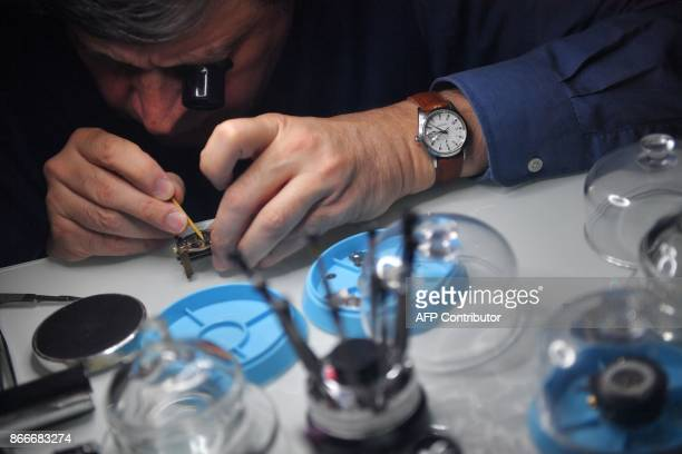 A watchmaker repairs a watch on October 26 2017 in Nantes western France two days before the end of Daylight Saving Time / AFP PHOTO / LOIC VENANCE