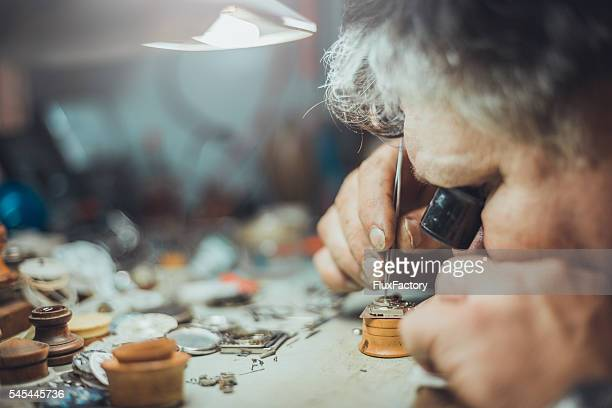 watchmaker repairs watch - picking parts with tweezers