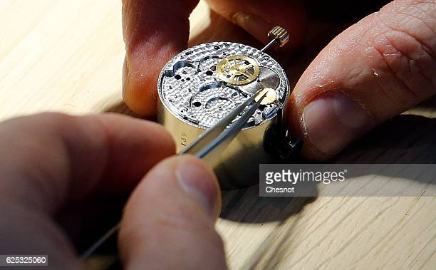 A watchmaker works on a mecanism of a Hermes luxury watch displayed during the 'Hermes hors les murs' event on November 23 2016 in Paris France The...