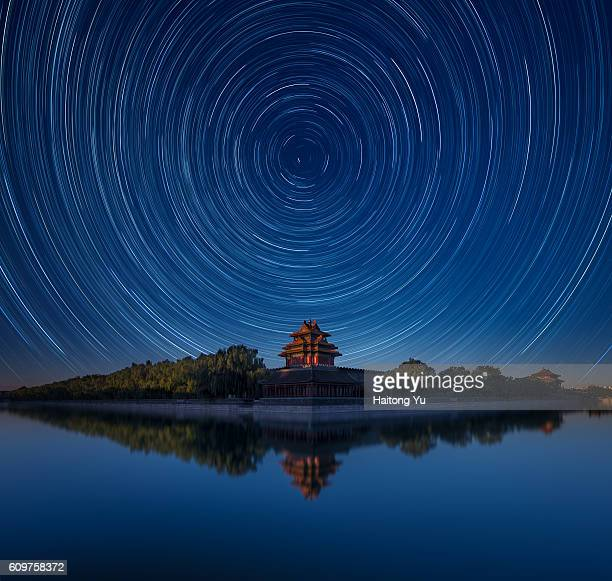 Watchtower of the Forbidden City, China, under night sky with startrails (composite image)