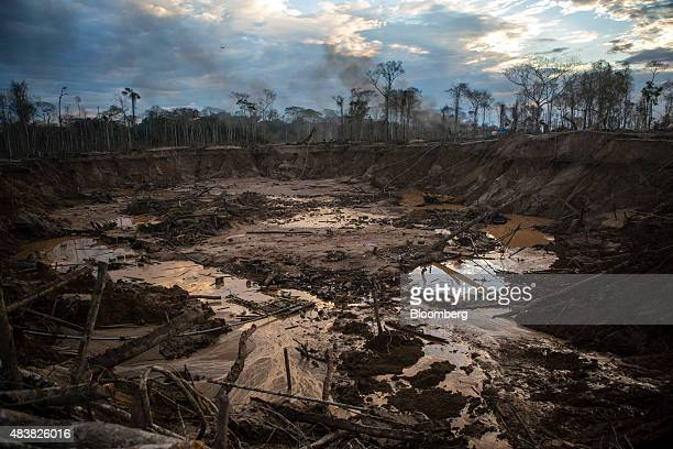 Water and debris gather in an open pit left behind by fleeing gold miners inside the Amazonian National Reserve buffering zone of Tambopata in Puerto...