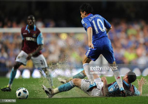 Water and mud sprays off the pitch as Wayne Bridge of West Ham United tackles Yossi Benayoun of Chelsea during the Barclays Premier League match...