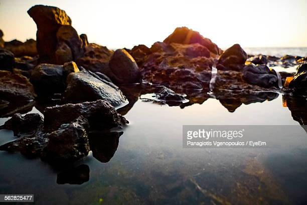 water and rocks against sky against sunset - vgenopoulos stock pictures, royalty-free photos & images