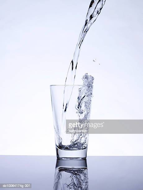 water being poured into glass, studio shot - glass of water stock pictures, royalty-free photos & images