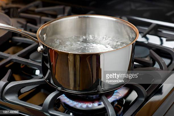 water boiling on a gas stove, stainless pot. - cooking pan stock pictures, royalty-free photos & images
