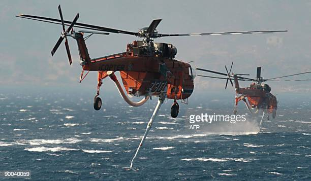 Water bomber helicopters fill in water to estinguish the fire atop the mountain in Porto Germeno some 70 km west of Athens on August 24 2009 A fire...