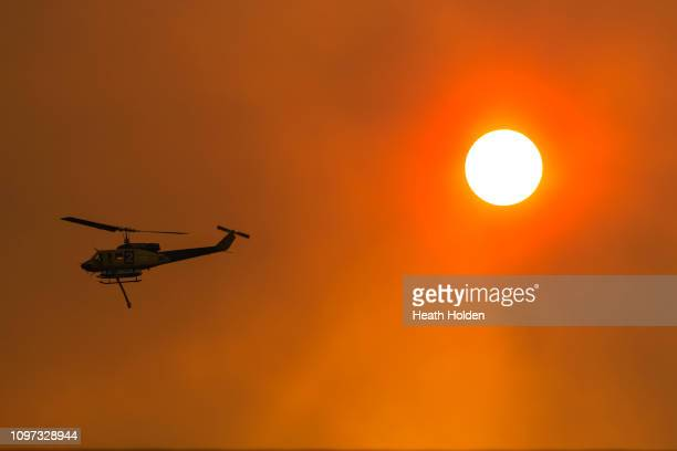 Water bombing helicopters working into the sunset to try and contain a large fire on January 21 2019 in Miena Australia The Tasmania Fire Service has...