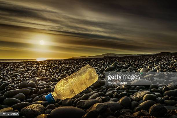 Water bottle on a rocky beach at sunset.