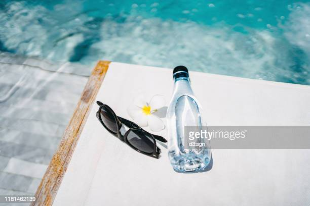 water bottle, sunglasses and flower petal on a deck chair by the swimming pool under sunshine, summer time fun, essentials, tourism and vacation concept - サングラス 無人 ストックフォトと画像