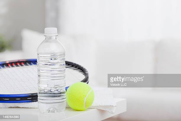 Water bottle, tennis racket and tennis ball on table, still life