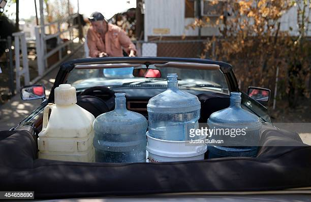 Water bottles to filled with nonpotable water sit in the back seat of JC Coates' car on September 4 2014 in Porterville California More than 300...