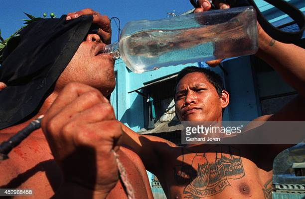 A water break for one of the 200 inmates who performed self flagellation on Good Friday to repent their crimes and to bring luck back to their...