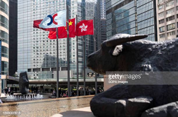 A water buffaloes sculpture created by late British artist Elisabeth Frink set in front of flags of Hong Kong China and The Stock Exchange of Hong...