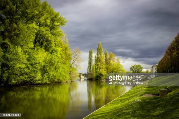 water canal with trees and storm clouds in background - yvelines stock pictures, royalty-free photos & images