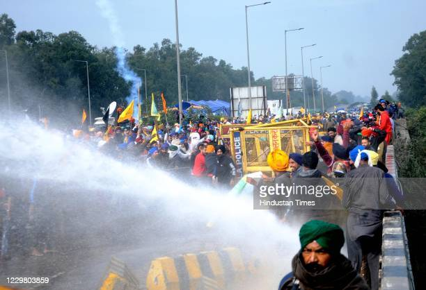 Water cannon is used on members of farmers groups trying to cross Shambu Border during the Delhi Chalo protest march against the new farm laws on...
