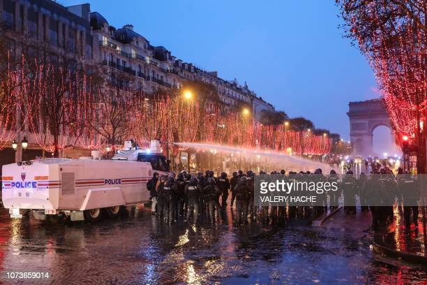 A water cannon sprays water on yellow vests protesters to disperse them during a demonstration against rising costs of living they blame on high...