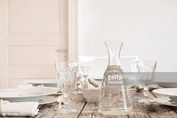 Water carafe and empty glasses on laid table