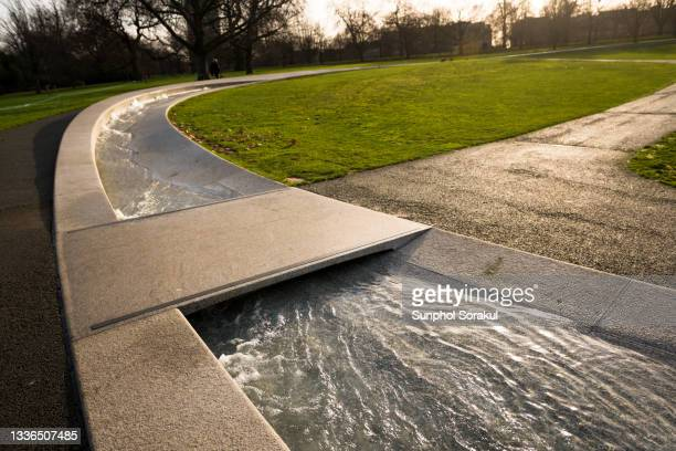 water channel with small bridge at the diana, princess of wales memorial fountain in hyde park, london - british royalty stock pictures, royalty-free photos & images
