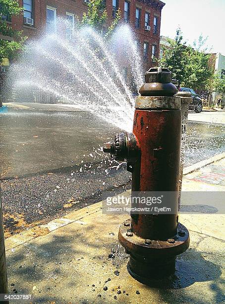 water coming out from fire hydrant in city - fire hydrant stock pictures, royalty-free photos & images