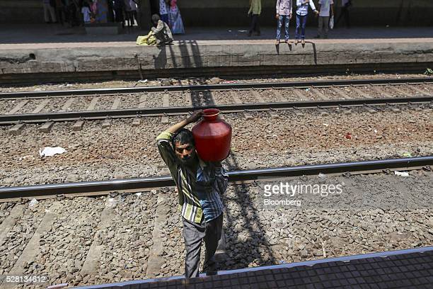 Water commuter carries a container of water across train tracks at Diva railway station in Mumbai, India, on Sunday, April 17, 2016. Hundreds of...