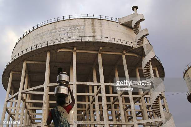 Water commuter carries a vessel of water on her head at the Vivekananda Chowk water tank in Latur, Maharashtra, India, on Saturday, April 16, 2016....