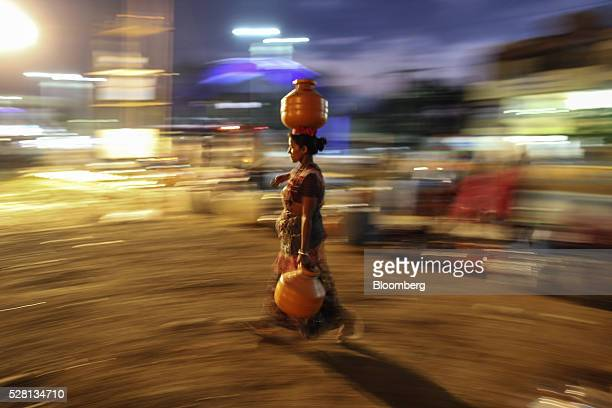 A water commuter carries a vessel of water on her head from the Vivekananda Chowk water tank in Latur Maharashtra India on Saturday April 16 2016...