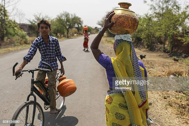 A water commuter carries a vessel of water on her head in Latur Maharashtra India on Saturday April 16 2016 Hundreds of millions of people in India...