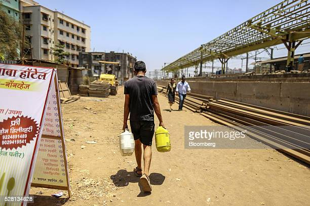 A water commuter carries water cans outside Diva railway station in Mumbai India on Sunday April 17 2016 Hundreds of millions of people in India are...