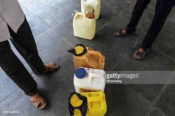 Water commuters stand next to water cans on a platform at Diva railway station in Mumbai, India, on Sunday, April 17, 2016. Hundreds of millions of...