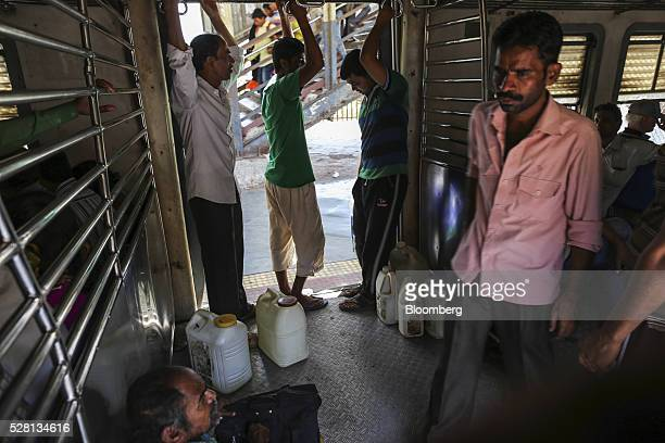 Water commuters transport water cans on a train traveling between Mumbra and Diva railway stations in Mumbai India on Sunday April 17 2016 Hundreds...